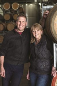 Greg and Kelli in front of Barrels - Greg Cooley Wines